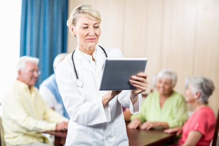 sheltered accommodation: Nurse using a tablet standing in a retirement home