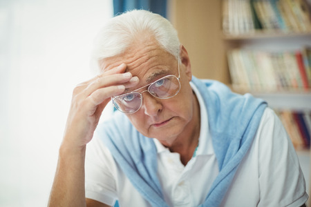unhappy man: Sad senior man sitting at table in a retirement home