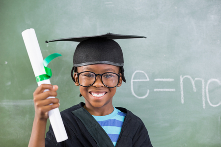 academic dress: Portrait of schoolboy in mortar board holding certificate in classroom at school Stock Photo