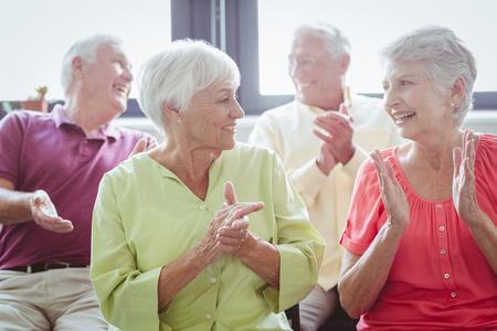 manos aplaudiendo: Las personas mayores que aplauden las manos en una casa de retiro Foto de archivo