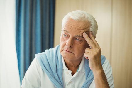 sheltered accommodation: Sad senior man touching his head in a retirement home