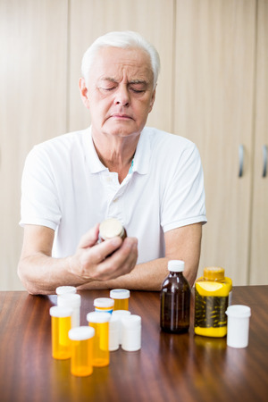 tailor seat: Senior looking at medicine in a retirement home Stock Photo