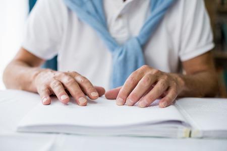 braille: Hombre mayor que usa braille para leer en una casa de retiro