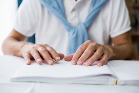 braille: Senior man using braille to read in a retirement home