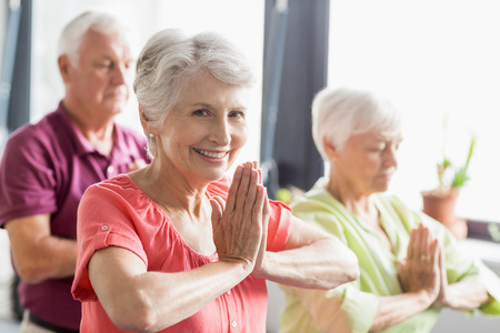 Seniors doing yoga with closed eyes in a retirement home Stock Photo