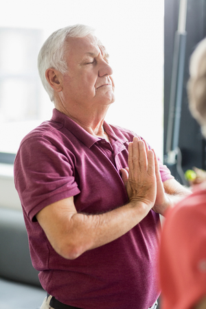 sheltered accommodation: Seniors doing yoga with closed eyes in a retirement home Stock Photo