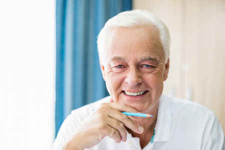 coloured pencil: Smiling senior holding coloured pencil in a retirement home