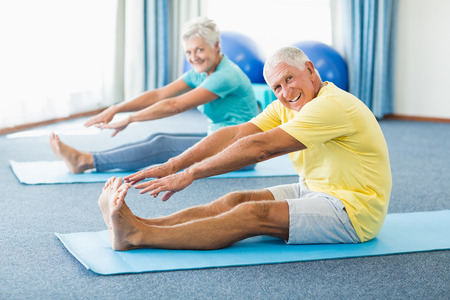 Seniors stretching legs in a studio