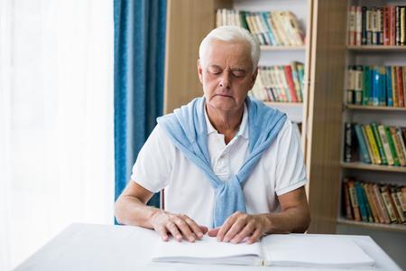 braile: Hombre mayor que usa braille para leer en una casa de retiro