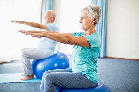 Les personnes âgées utilisant ballon d'exercice dans un studio Banque d'images