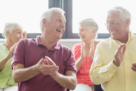 Seniors clapping hands in a retirement home Stock Photo