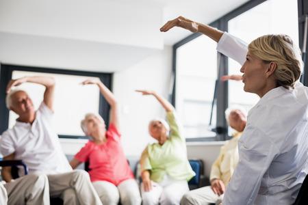 Senioren doend uitgeoefend in een bejaardentehuis Stockfoto