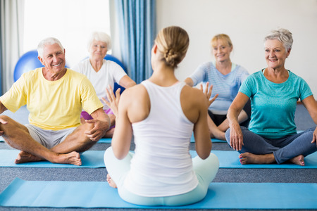 tailor seat: Instructor performing yoga with seniors during sports class