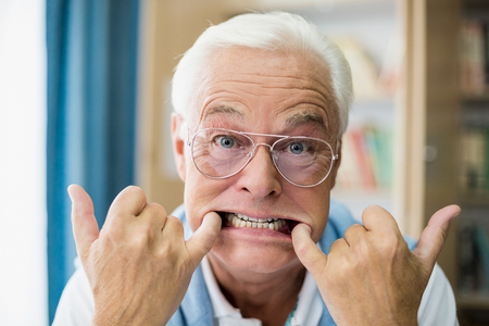 making faces: Senior man making faces in a retirement home Stock Photo