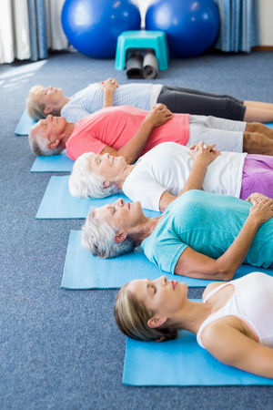 nursing class: Instructor performing yoga with seniors during sports class