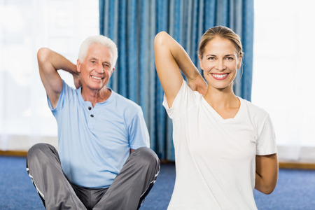 nursing class: Instructor helping senior man with sport exercises during sports class