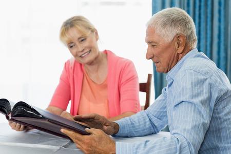 Pares mayores que miran el álbum de fotos en una casa de retiro