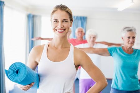 nursing class: Instructor holding yoga mat during sports class