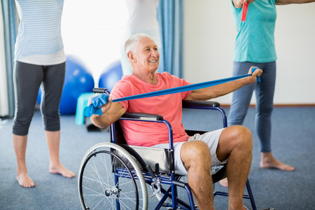 sheltered accommodation: Senior in wheelchair exercising with exercising band during sports class Stock Photo