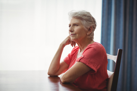 nursing class: Thoughtful senior woman sitting at a table in a retirement home