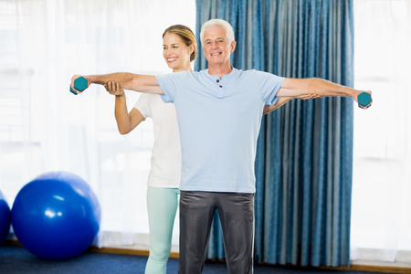 nursing class: Instructor helping senior man with weights during sports class