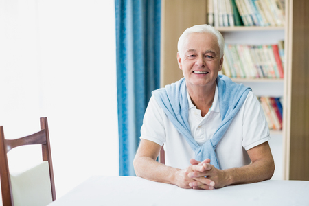 Senior man zit aan een tafel in een bejaardentehuis