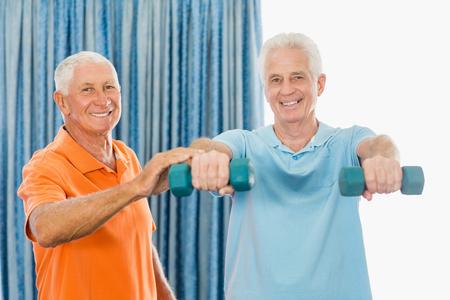 senior exercising: Senior exercising with weights in a studio Stock Photo