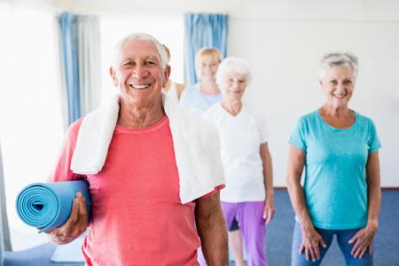 nursing class: Senior man holding yoga mat during sports class Stock Photo