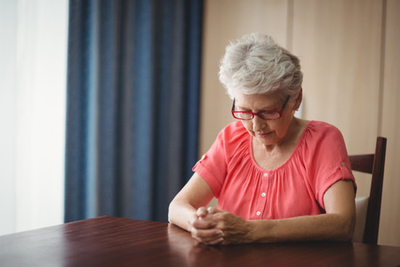 desolación: Thoughtful senior woman sitting at a table in a retirement home