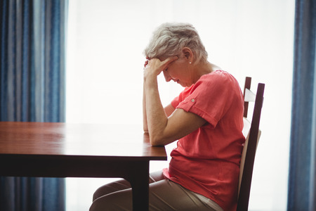 desolación: Sad senior woman sitting at a table in a retirement home