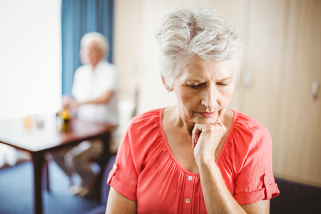 sheltered accommodation: Thoughtful senior woman touching her chin in a retirement home