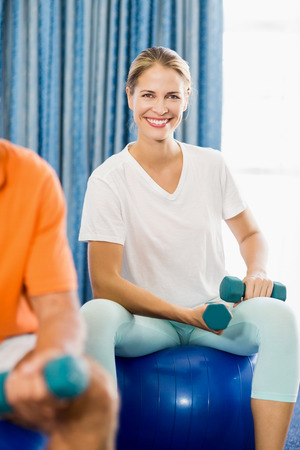 nursing class: Instructor using exercise ball and weights during sports class