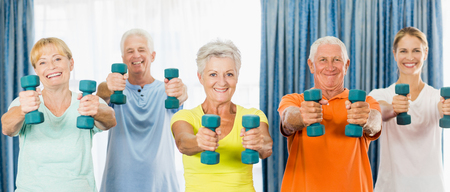 nursing class: Seniors exercising with weights during sports class Stock Photo