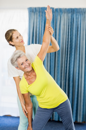 nursing class: Instructor helping senior woman with sport exercises during sports class