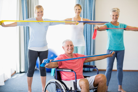 sheltered accommodation: instructor and seniors exercising with stretching bands during sports class Stock Photo