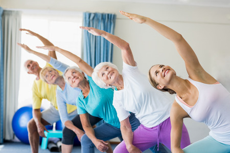sheltered accommodation: Instructor performing yoga with seniors during sports class