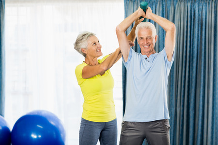 nursing class: Senior man using weights in a sport studio Stock Photo