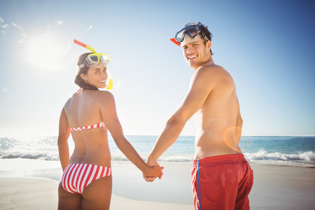 diving mask: Portrait of happy young couple wearing diving mask standing on beach Stock Photo