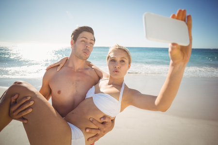bikini couple: Happy young couple taking selfie with mobile phone on beach Stock Photo