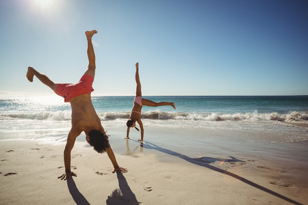 somersault: Couple performing somersault on beach in summer