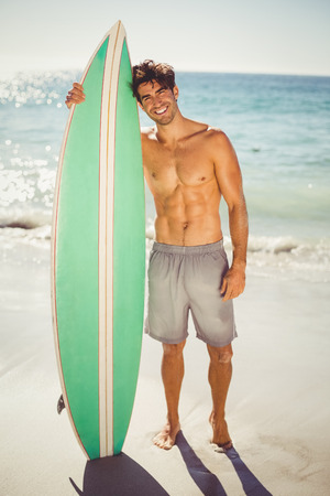 romance strategies: Portrait of happy man posing with surfboard on beach