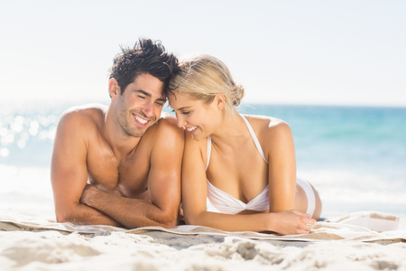 bikini couple: Romantic young couple lying on beach