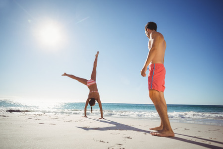somersault: Man watching woman while performing somersault on beach