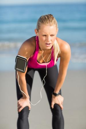 taking a break: Tired sportswoman taking a break on beach