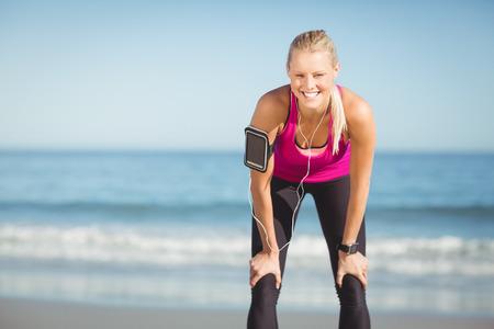 taking a break: Portrait of happy sportswoman taking a break on beach