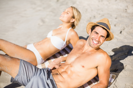 romance strategies: Happy young couple lying on beach Stock Photo