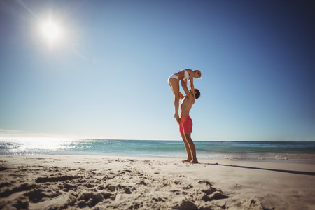 romance strategies: Man lifting woman at beach on a sunny day