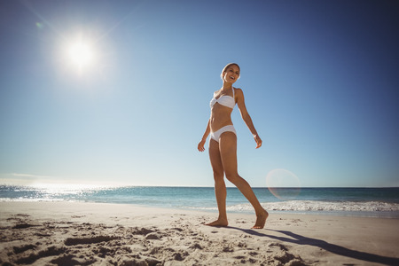senior adult woman: Beautiful young woman walking on beach in summer
