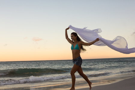 scarf beach: Woman running with a scarf on the beach