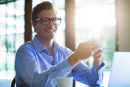 phone message: Portrait of smiling man using mobile phone in restaurant